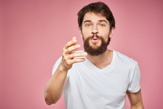 Leuke bebaarde mannen witte t-shirt studio roze geïsoleerde achtergrond