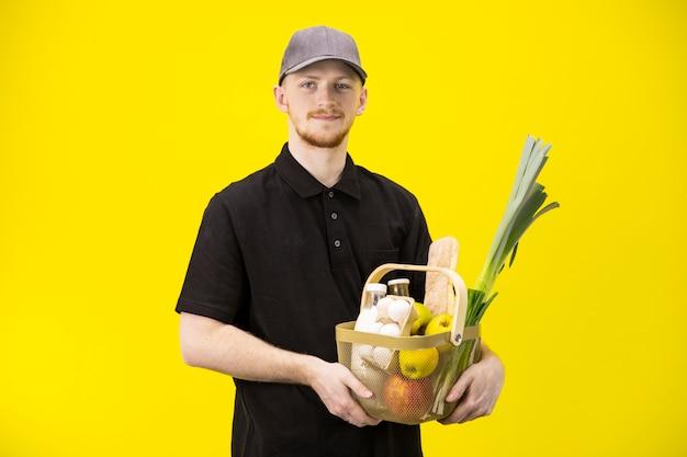 Leuke bezorger houdt mand met eco-producten van de boerderij, bezorgservice voor eten