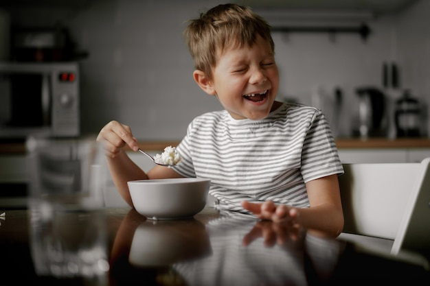 Leuke blanke 6-jarige jongen die havermout eet als ontbijt en lacht
