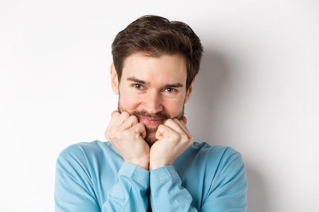 Leuke blanke man die naar iets kijkt met bewondering en verlangen, gezicht aanraakt met een domme glimlach, staande op een witte achtergrond.