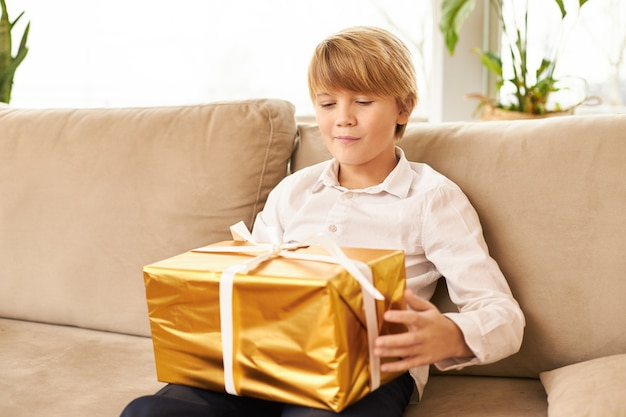 Leuke blanke tiener zittend op de bank met een nieuwjaarscadeau op zijn schoot. knappe jongen klaar om gouden doos met kerstcadeau erin te openen, nieuwsgierig verwachtte gezichtsuitdrukking, glimlachend