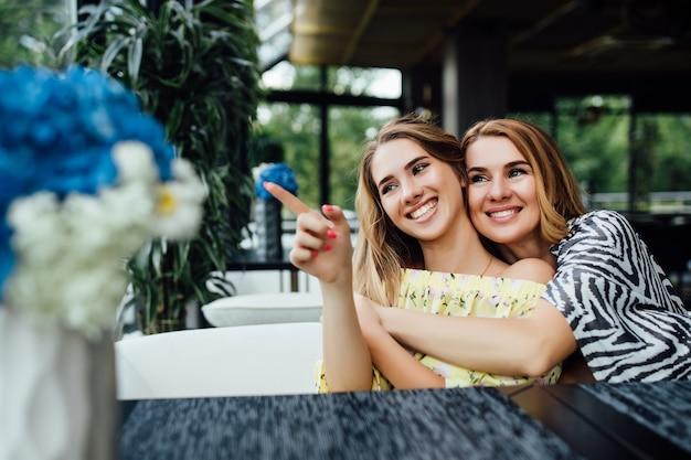 Leuke, blonde jonge dochter die haar moeder met liefde omhelst en ernaar uitkijkt op het zomerterras in restaurant
