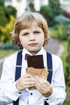 Leuke blonde kerel, schooljaren gekleed in schooluniform met plezier zwarte chocolade eten op straat in het park