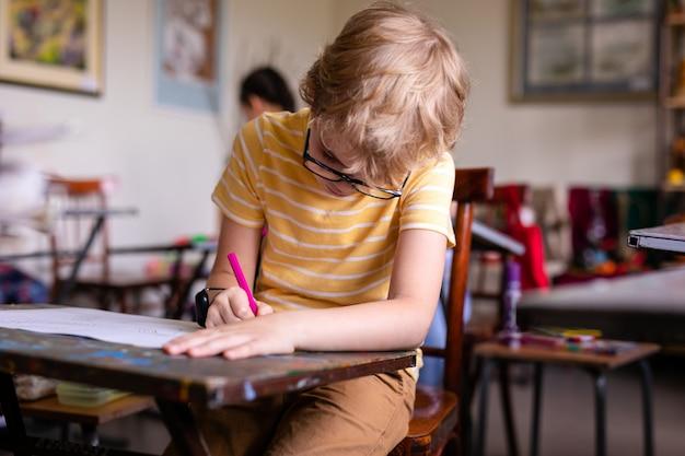 Leuke blonde schoolstudent die met modieuze glazen in klaslokaal schrijven
