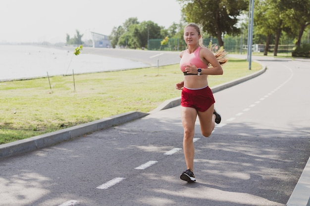 Leuke blonde sportieve vrouw met lang haar jogt in het park