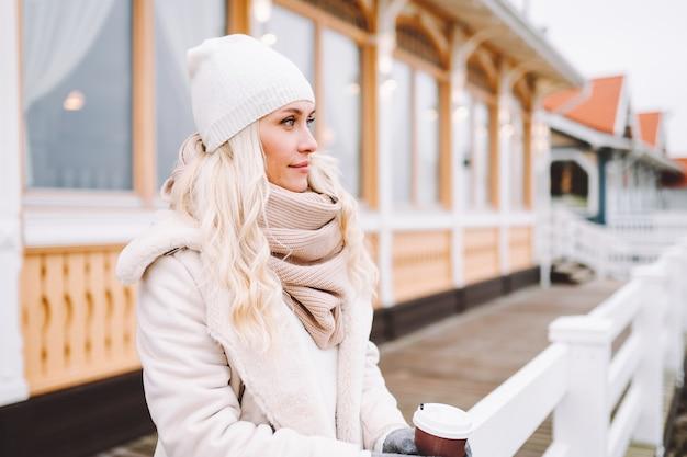 Leuke blonde vrouw van middelbare leeftijd geniet van tijd buiten op winterdag. vrouw draagt een licht jasje, hoed, sjaal en heeft warme drank.