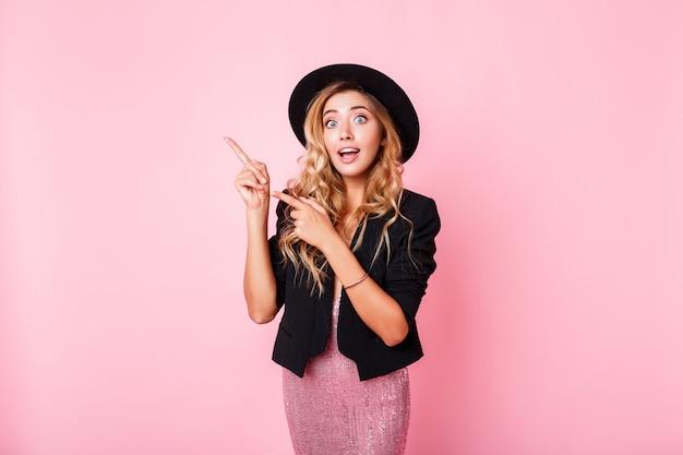 Leuke blondevrouw die met verrassingsgezicht door vinger op één of ander ding richten, die zich over roze muur bevinden. het dragen van trendy jurk met sequentie, zwarte jas en hoed.