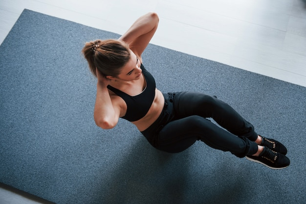 Leuke blondine. buikspieren op de vloer in de sportschool. mooie vrouwelijke fitness vrouw