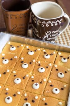 Leuke botercakes op bakdienblad met koffiekop op de lijst.