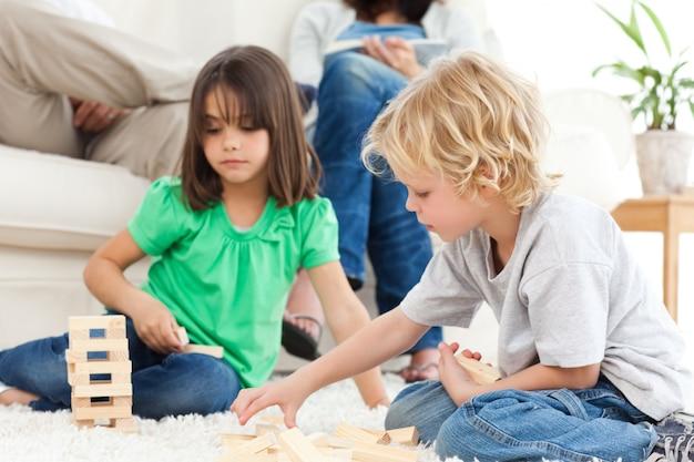 Leuke broer en zus spelen met dominostenen op de vloer