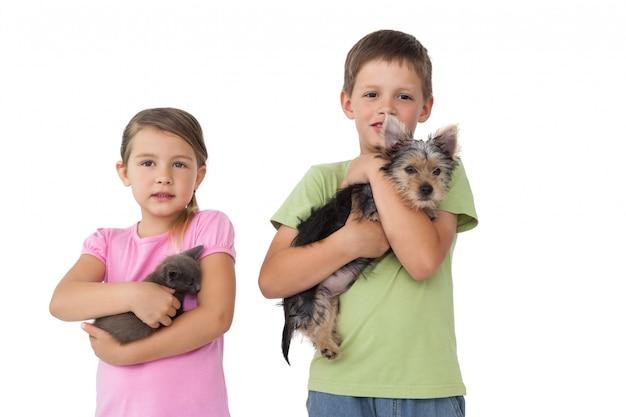 Leuke broers en zussen die hun huisdieren houden en bij camera glimlachen