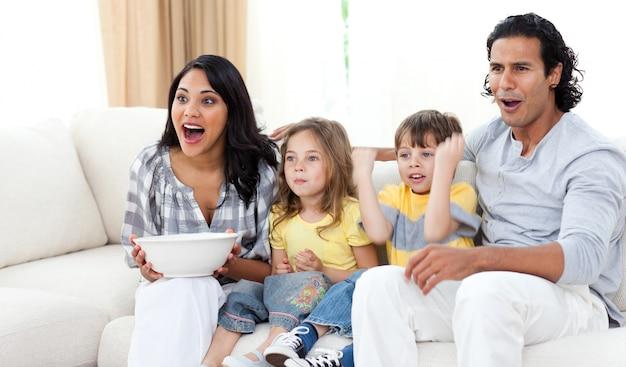 Leuke broers en zussen die tv kijken met hun ouders