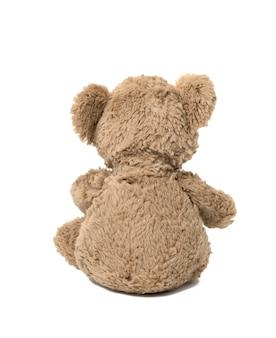 Leuke bruine teddybeer die achterover leunt op een witte geïsoleerde achtergrond