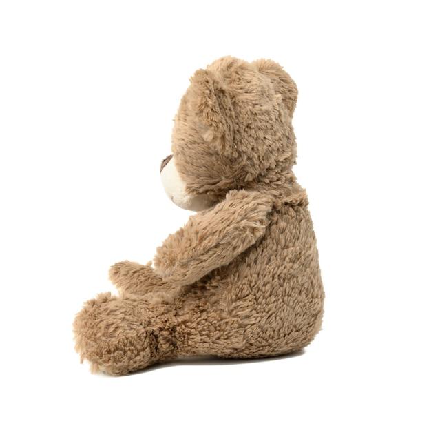 Leuke bruine teddybeer die zijwaarts op een witte geïsoleerde achtergrond zit