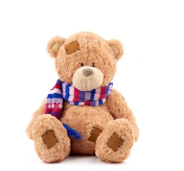 Leuke bruine teddybeer met patches in een gekleurde gebreide sjaal