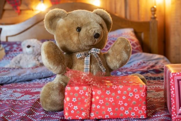 Leuke bruine teddybeer zit op bed in de buurt van rode kerst- en oudejaarsgeschenkdoos met strik, cadeautjes voor kinderen