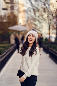 Leuke brunette in een witte trui in een stad