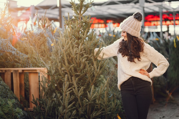 Leuke brunette in een witte trui met kerstboom