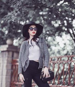 Leuke brunette met rode lippen in hoed en zonnebril die in stad stellen