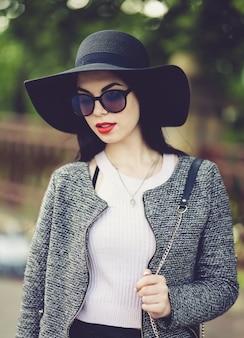 Leuke brunette met rode lippen in zonnebril die in stad stellen