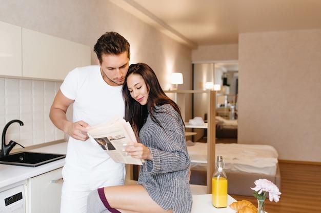 Leuke brunette vrouw in wollen jurk krant lezen met vriendje genieten van smakelijke maaltijd in de ochtend