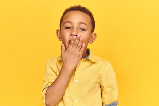 Leuke charmante afrikaanse leerling die gezichtsuitdrukking heeft uitgeput die mond behandelt geeuwt wordt moe na school. schooljongen met een donkere huidskleur die zich slaperig voelt door vroeg ontwaken