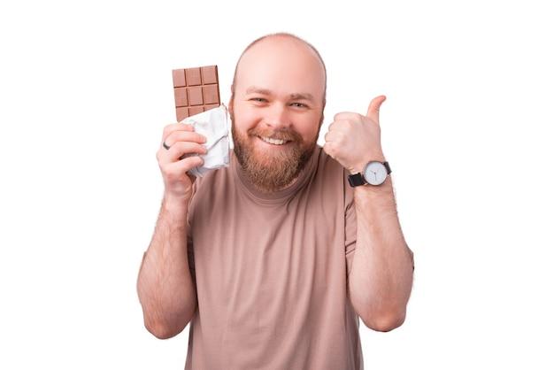 Leuke charmante jonge bebaarde man met blok chocolade en duim opdagen