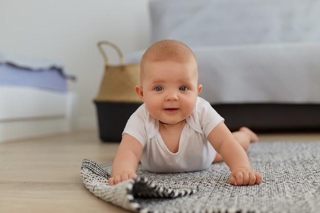 Leuke charmante kleine babyjongen of -meisje die op de vloer ligt en probeert te kruipen, witte kleding draagt, naar de camera kijkt, alleen plezier heeft binnen, gelukkige jeugd.