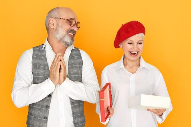 Leuke charmante vrouw van middelbare leeftijd in stijlvolle hoofddeksels mond openen in opwinding tijdens het openen van doos met cadeau van haar man op verjaardag, bebaarde senior man handen wrijven met plezier