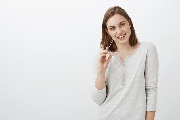 Leuke collega hebben en oog op charmante kerel flirten tijdens pauze bijten brillen brillen in de hand houden glimlachend teder poseren tegen grijze muur in casual witte blouse
