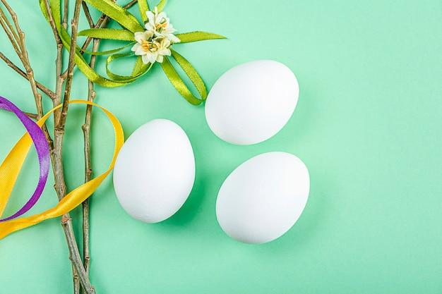 Leuke creatieve pasen-samenstelling met witte eieren, wilgentwijgen en kleurrijke linten op groene achtergrond. diy en kinderen creativiteit. zelfgemaakt ambacht. wenskaart, mock-up. kopieer ruimte voor tekst