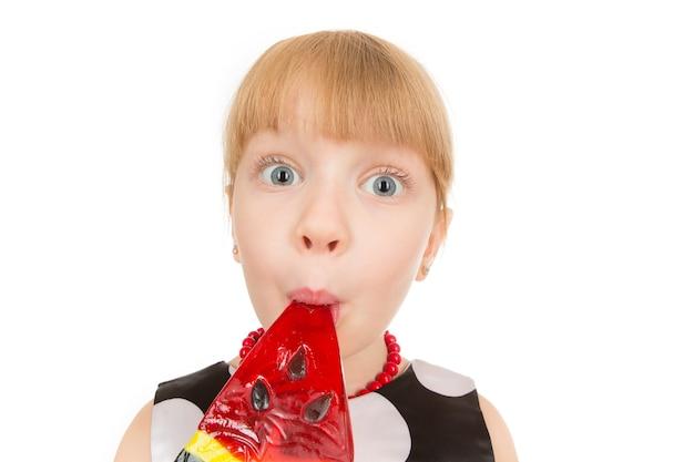 Leuke dag. close-up shot van een klein meisje snoep eten met een grappig gezicht