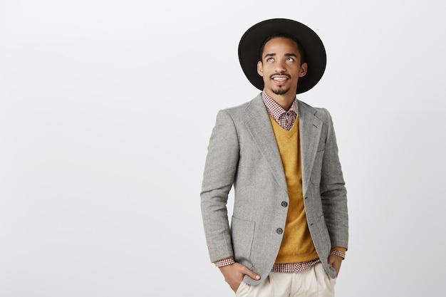 Leuke dag om miljarden te verdienen. portret van rijke knappe zakenman in stijlvolle formele outfit en hoed opzoeken, geïnteresseerd en vermaakt met merkwaardige dingen, dromen over grijze muur