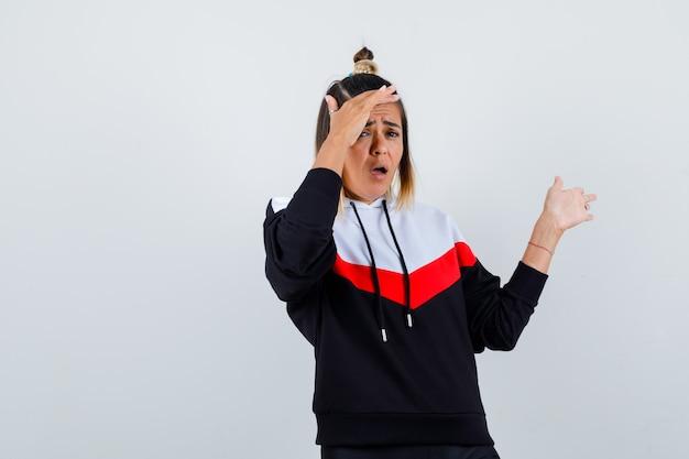 Leuke dame die hand boven het hoofd houdt, palm opzij spreidt in hoodie en verrast kijkt. vooraanzicht.