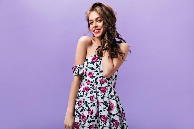 Leuke dame in een stijlvolle jurk op zoek naar camera. langharige vrouw in stijlvolle zomer outfit poseren en lachend op paarse achtergrond.