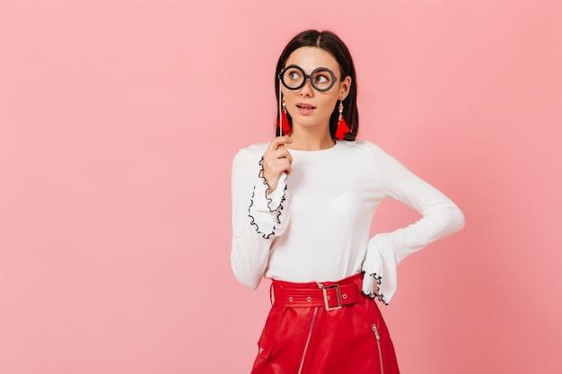 Leuke dame in rode rok vormt met attribuut voor fotoshoot in de vorm van een bril. portret van brunette met interesse opzij kijken op roze achtergrond.