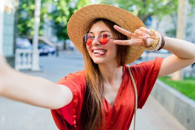 Leuke dame in stijlvolle hoed selfie maken tijdens het wandelen buiten in de zomerweekends
