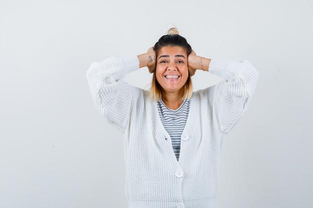 Leuke dame in t-shirt, vest omklemd hoofd met handen en ziet er gelukkig uit