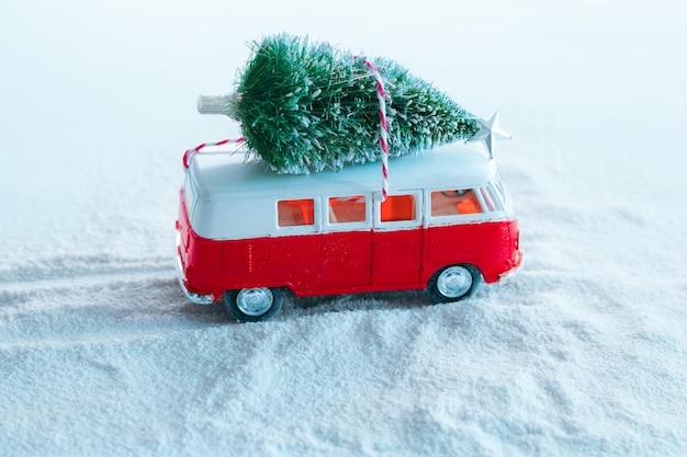 Leuke de vakantieboom van de de wintervakantie kerstmisboom op retro stuk speelgoed vrachtwagen in sneeuwbos