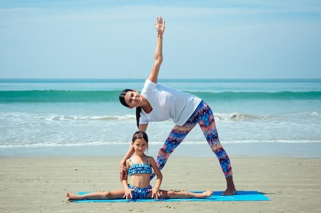Leuke dochter en mooie moeder die yoga beoefenen en samen op het strand mediteren