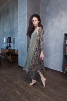Leuke donkerbruine vrouw die thuis in haar lange nachtkleding loopt en geniet.