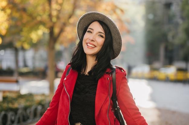Leuke donkerbruine vrouw die zich in park met gelukkige glimlach bevindt
