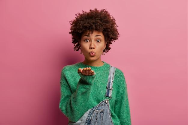 Leuke donkere etnische vrouw houdt de lippen rond, stuurt een zoete luchtkus