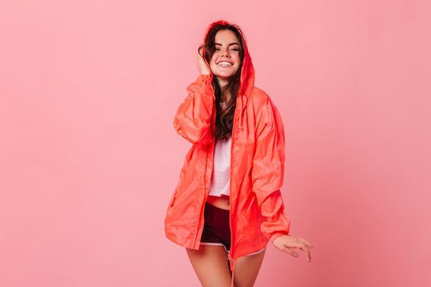 Leuke donkerharige vrouw in wit t-shirt en oranje windjack lacht op roze muur