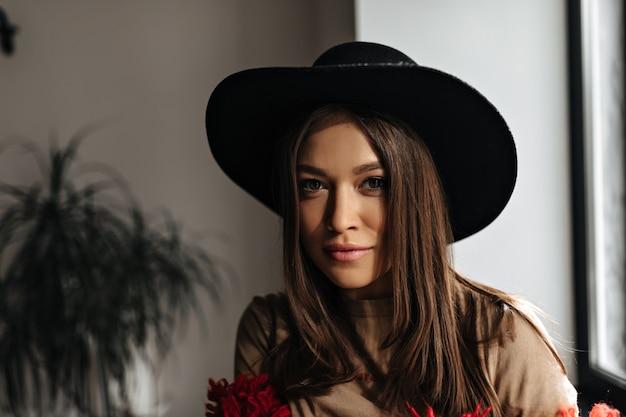 Leuke donkerharige vrouw met een gebruinde huid kijkt naar de camera. vrouw in zwarte hoed en beige t-shirt poseren in lichte kamer.