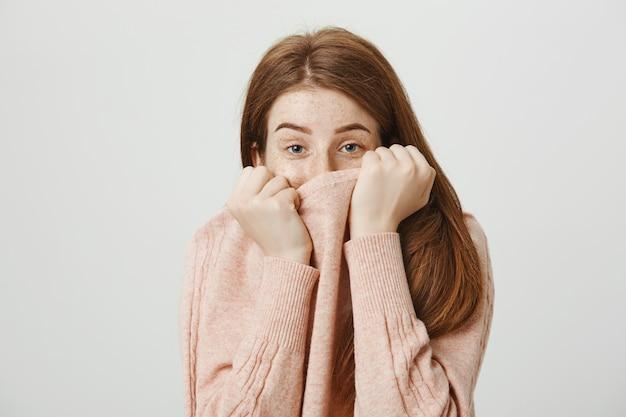 Leuke dwaze roodharige vrouw verbergt gezicht achter trui kraag en ziet er verlegen uit