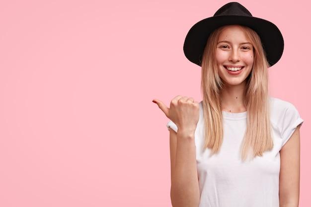 Leuke elegante jonge europese vrouw gekleed in een wit t-shirt en draagt een zwarte hoed