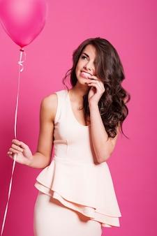 Leuke elegante vrouw met roze ballon