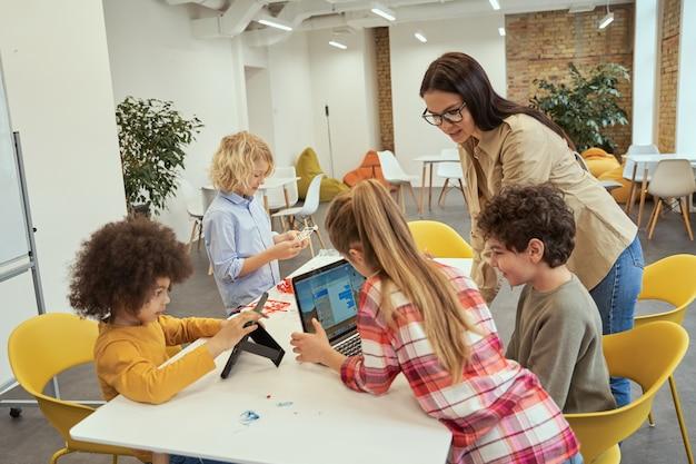 Leuke en boeiende gelukkige kinderen die gadgets gebruiken tijdens stamles met jonge vrouwelijke leraar