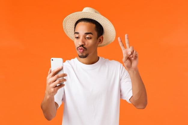 Leuke en gelukkige afro-amerikaanse man in wit t-shirt, zomerhoed, vredesteken tonen, selfie nemen met lippen van filtervouwlippen, smartphone kijken, foto's van vakantie posten, oranje